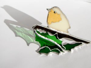 Standing white bird with green holly stained glass decor.