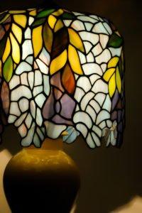 Szklany witrażowy klosz stojącej lampy stołowej.