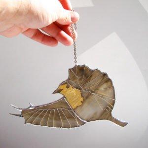 Witrażowy złocony szary ptak zornamentem.