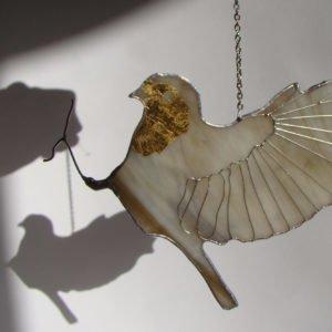 Witrażowy złocony ptaszek znóżką.
